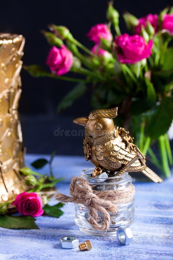 Steampunk broncea el pájaro en la taza de cristal en la bandeja de madera azul imagen de archivo