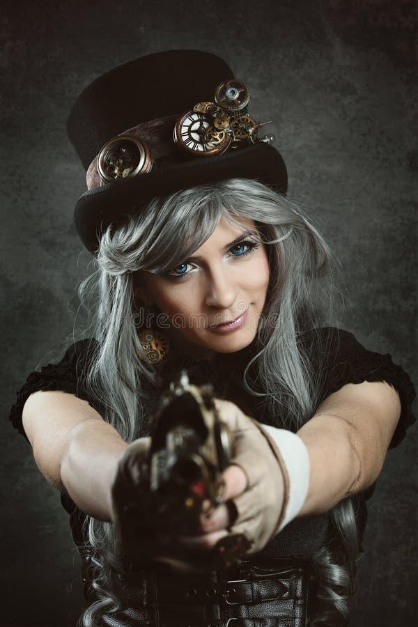 Steampunk-Frau, die ein Gewehr zeigt stockbild