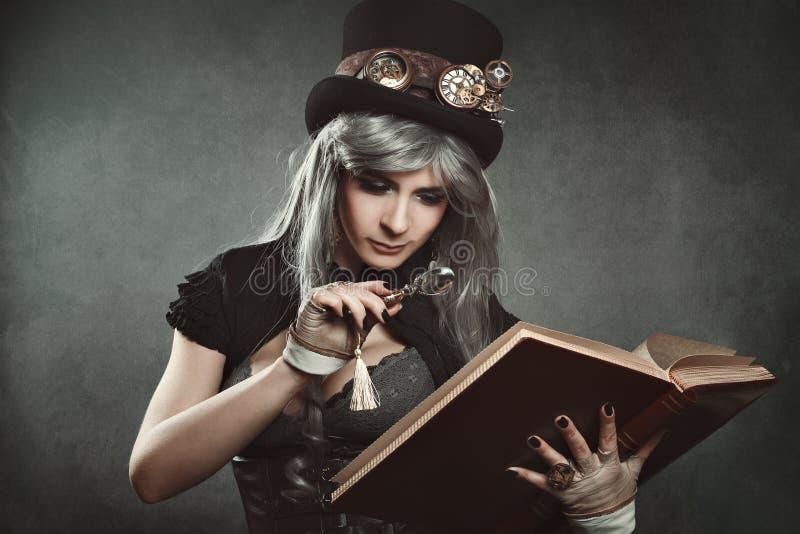 Steampunk-Frau mit Buch und Linse stockbilder
