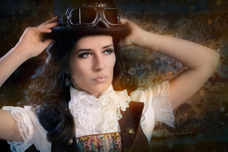 Steampunk Girl with Top Hat and Aviator Glasses. Portrait of a young woman wearing a steampunk outfit with top hat and aviator glasses royalty free stock images