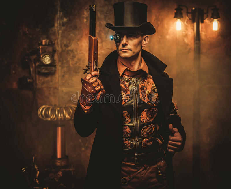 Steampunk man with gun on vintage steampunk background.  stock photography