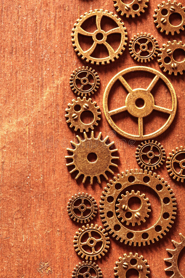 Steampunk mechanical cogs gears wheels on wooden background stock photo