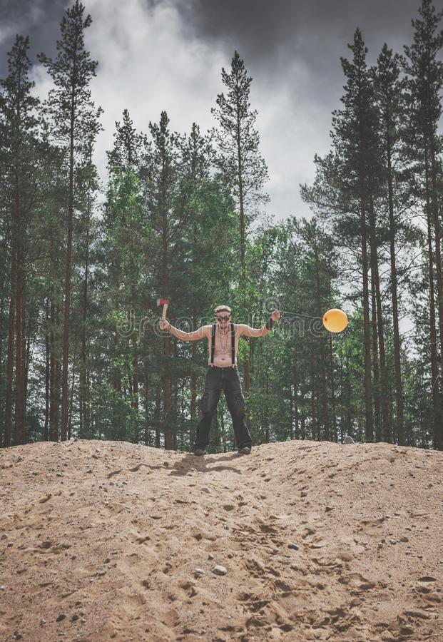 Steampunk style Man in glasses with ax and balloon standing on t stock photography