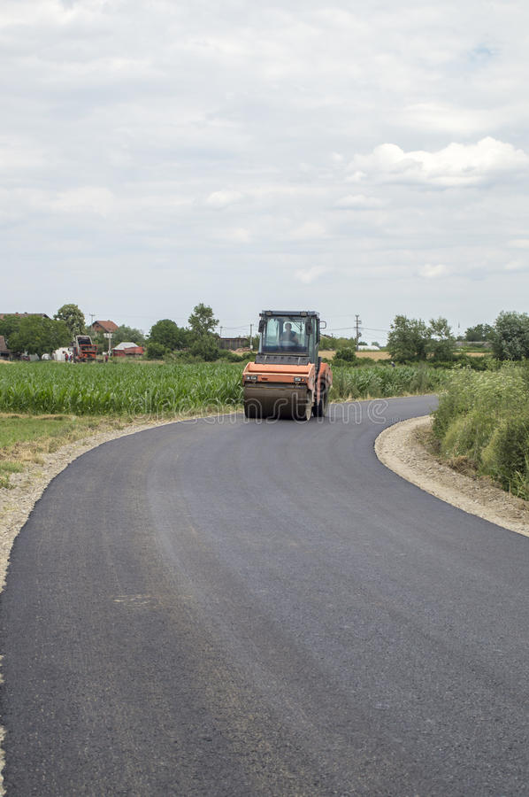 Steamroller flattens fresh asphalt royalty free stock images