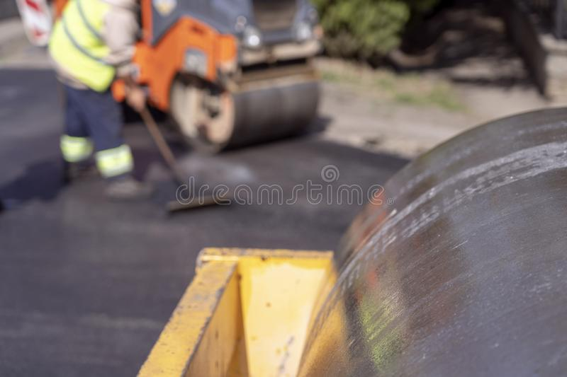 Steamroller and Road Construction Workers at Road Construction Site. Tarmac Laying Works at a Road Construction Site. Hot Asphalt Gravel Leveled by workers stock photo