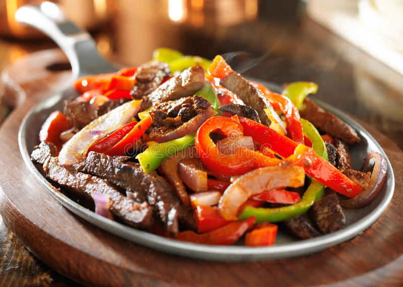 Steamy hot mexican beef fajitas. Shot close up in iron skillet royalty free stock photography