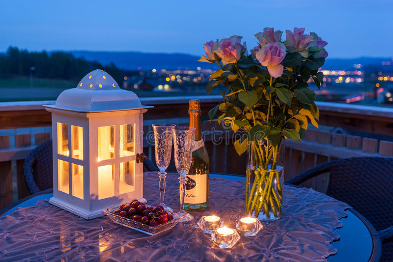 Stearinljus, Champagne och rosor på farstubron arkivbilder