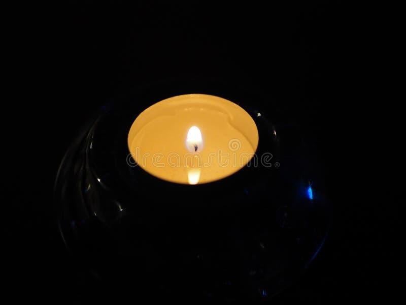 Stearinljus i det mörka guld- ljuset av stearinljusflamman arkivbild