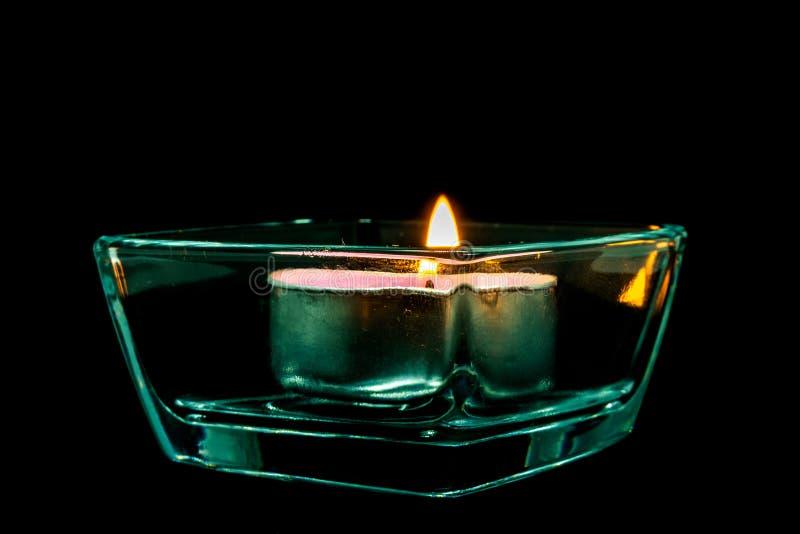 Stearinljus i exponeringsglasformen på en svart bakgrund, isolat arkivbilder