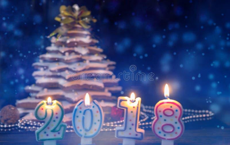 Stearinljus i form av 2018 nya år nära hemlagad pepparkaka C royaltyfri fotografi