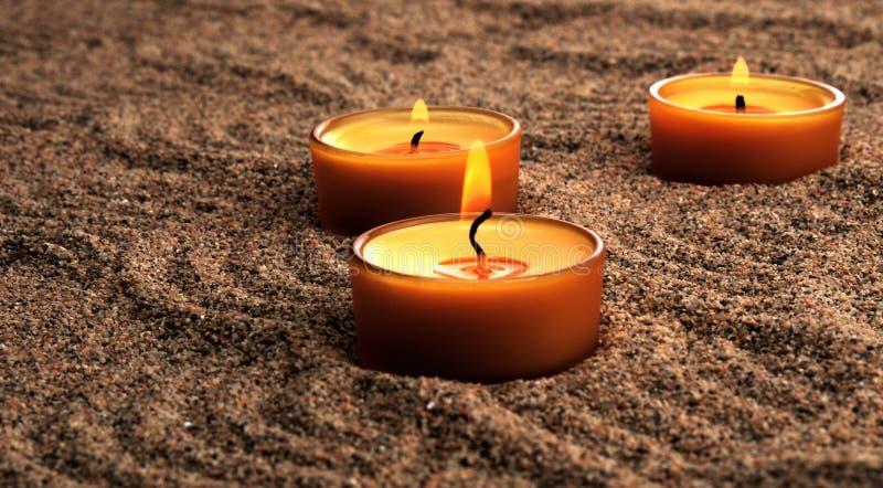 Stearinljus i sanden Lugna modeller på sanden royaltyfri bild