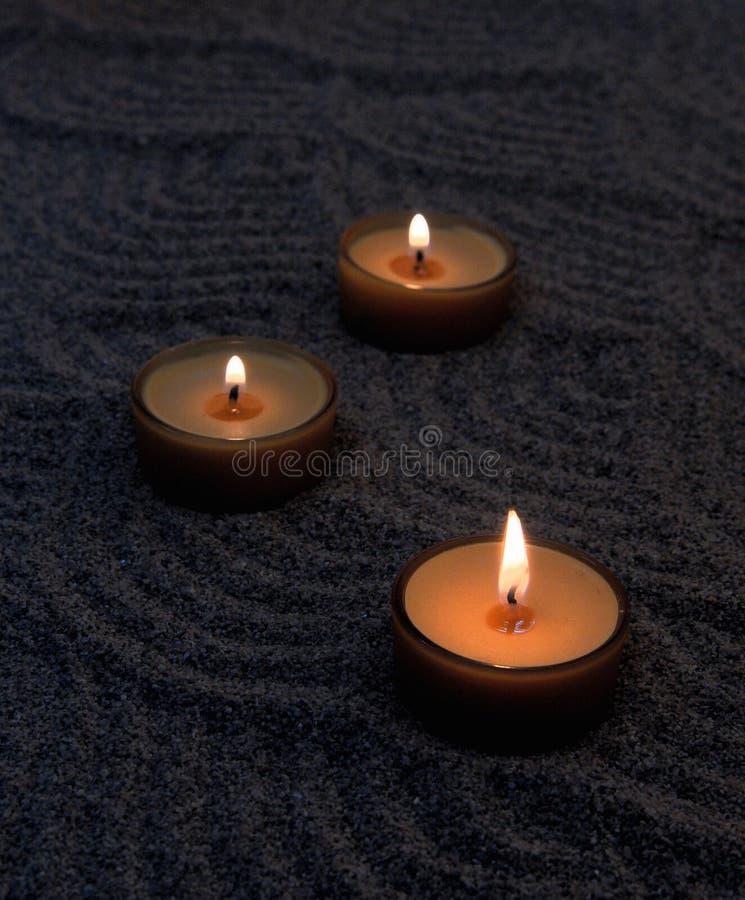 Stearinljus i sanden Lugna modeller på sanden fotografering för bildbyråer