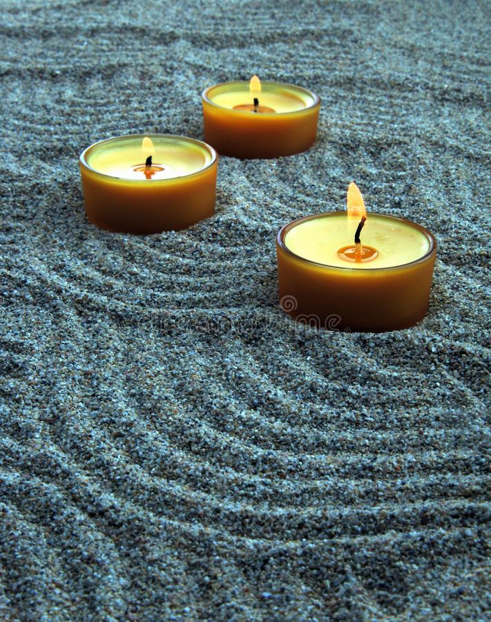 Stearinljus i sanden Lugna modeller på sanden arkivfoton