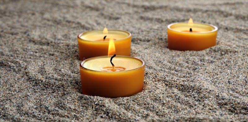Stearinljus i sanden Lugna modeller på sanden arkivbilder