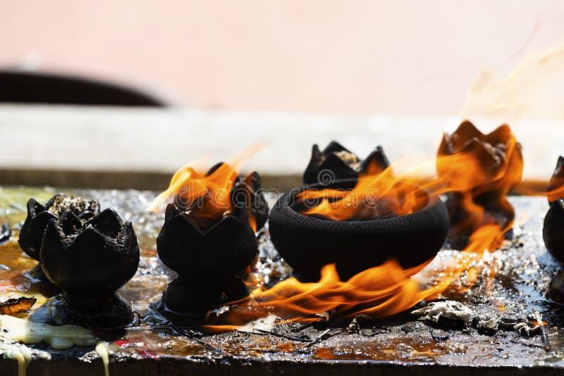 Stearinljus i templet Brand i lyktan för ber med Buddhastatyn i tempel arkivfoto