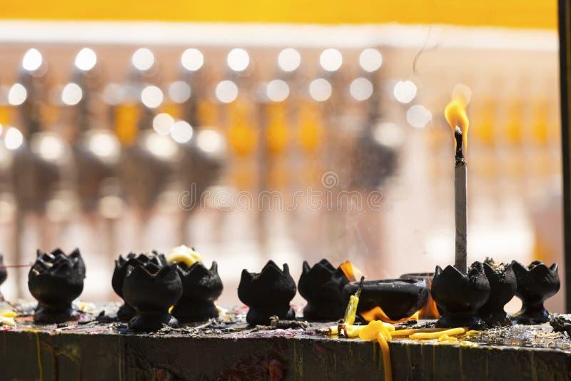 Stearinljus i templet Brand i lyktan för ber med Buddhastatyn i tempel royaltyfri fotografi