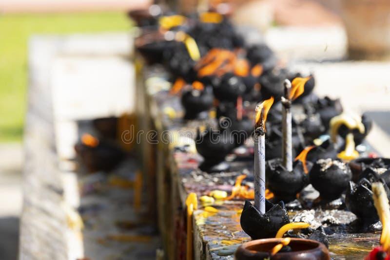 Stearinljus i templet Brand i lyktan för ber med Buddhastatyn i tempel royaltyfria bilder
