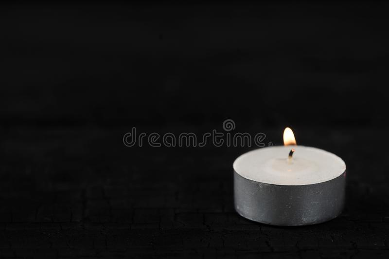 Stearinljus med bränningbrand på svart arkivbild