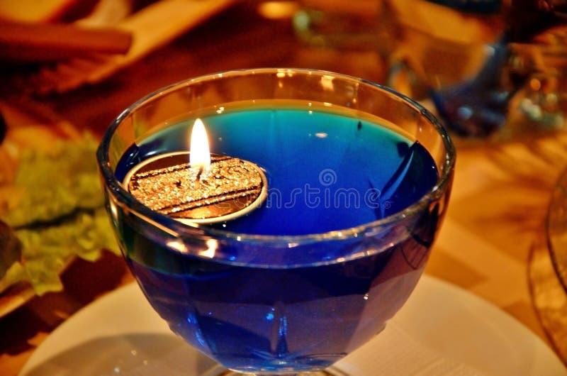 Stearinljus med brandflöten i en exponeringsglasskyttel med blått vatten Tabelldekor för nytt år fotografering för bildbyråer