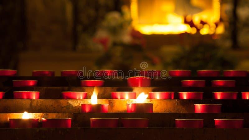 Stearinljus med flammainsidan en kyrka royaltyfria bilder