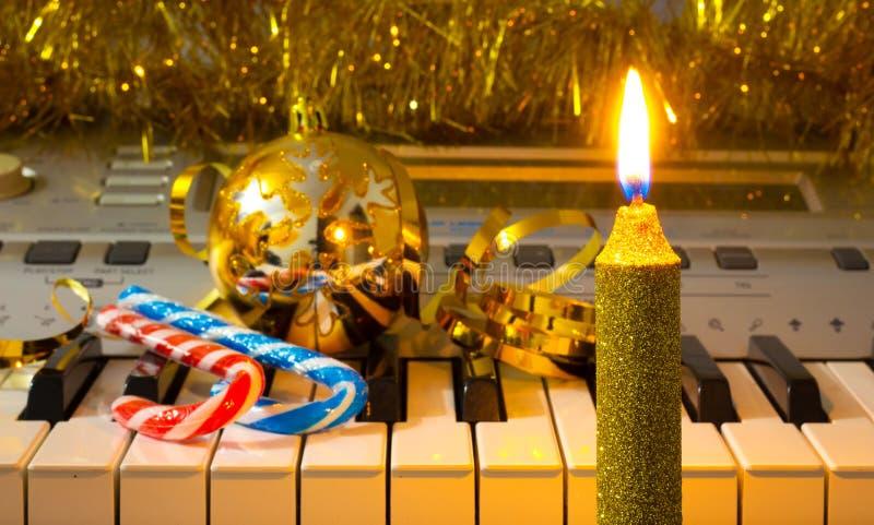 Stearinljus med julpynt nära pianot Festlig julnight_ royaltyfri foto