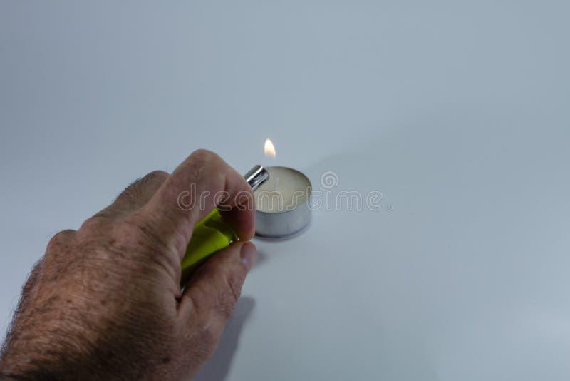 Stearinljus och grön tändare med handen på vit bakgrund arkivfoton