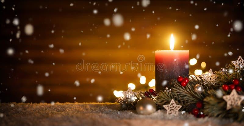 Stearinljus- och julgarnering med träbakgrund och snö royaltyfria foton