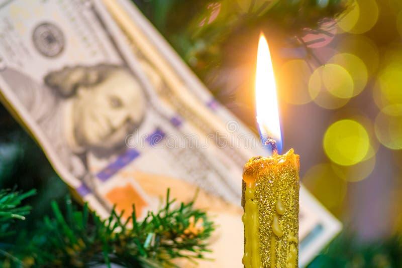 Stearinljus på bakgrunden av en julgran som dekoreras med dollarräkningar Rikedom och lycka i den nya Year_en arkivbild