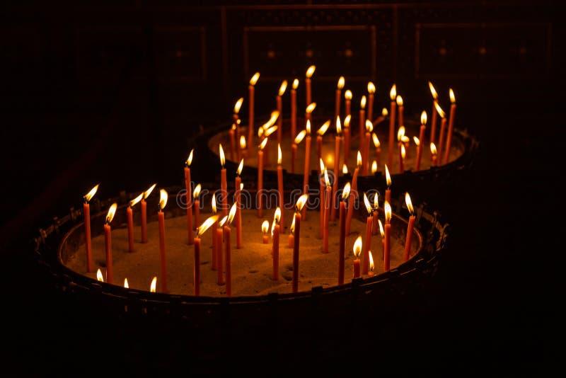 Stearinljus tände i en ställning med sand i en kyrka i Prague royaltyfri foto