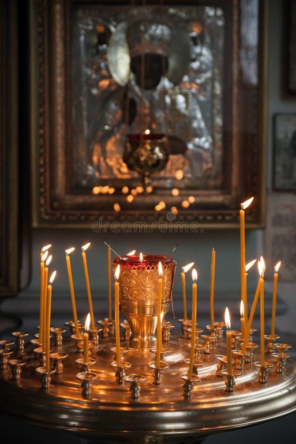 Stearinljus tänds i en mörk ortodox kyrka royaltyfri bild