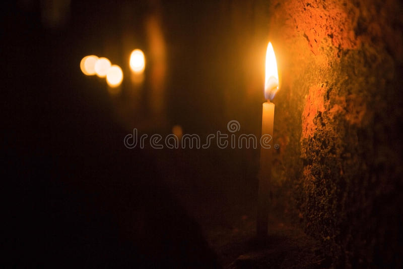 Stearinljuset på natten på en vägg royaltyfria foton