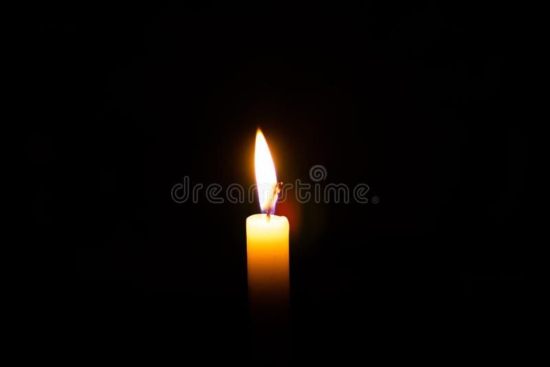 Stearinljusflamma mot isolerat på svart bakgrund, arkivfoto