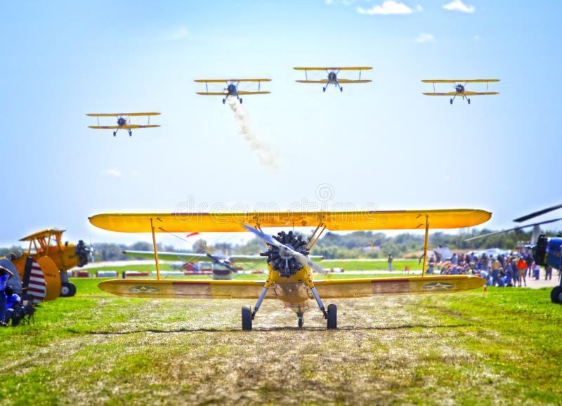 Stearman biplane. Yellow Stearman biplane and planes in formation royalty free stock photos