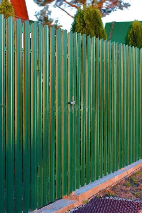 Steccato di metallo verde a con luci di tramonto fotografia stock