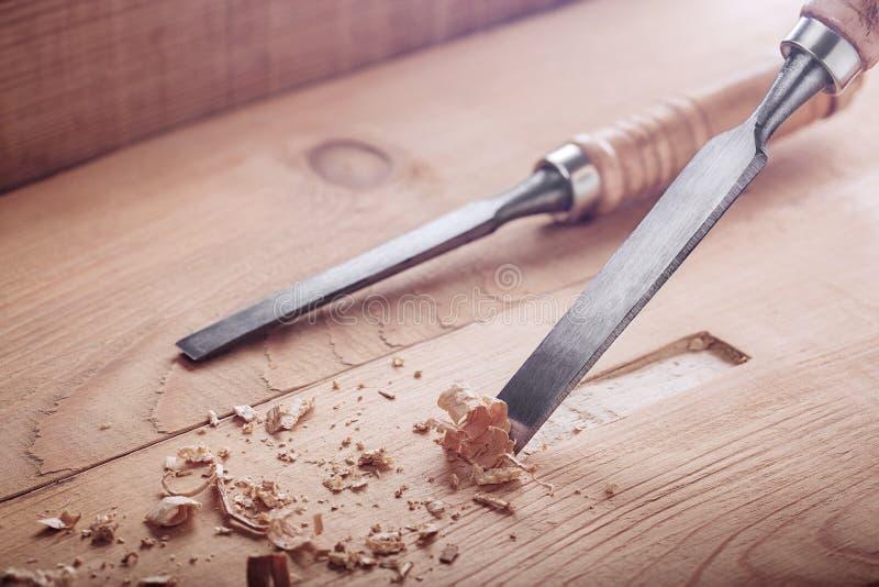 Stechbeitel, der Nut in der alten Kiefernplanke für das Türschloss herausschneidet stockfoto