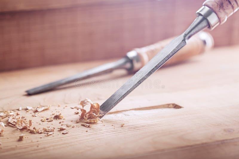 Stechbeitel, der Nut in der alten Kiefernplanke für das Türschloss herausschneidet lizenzfreies stockfoto