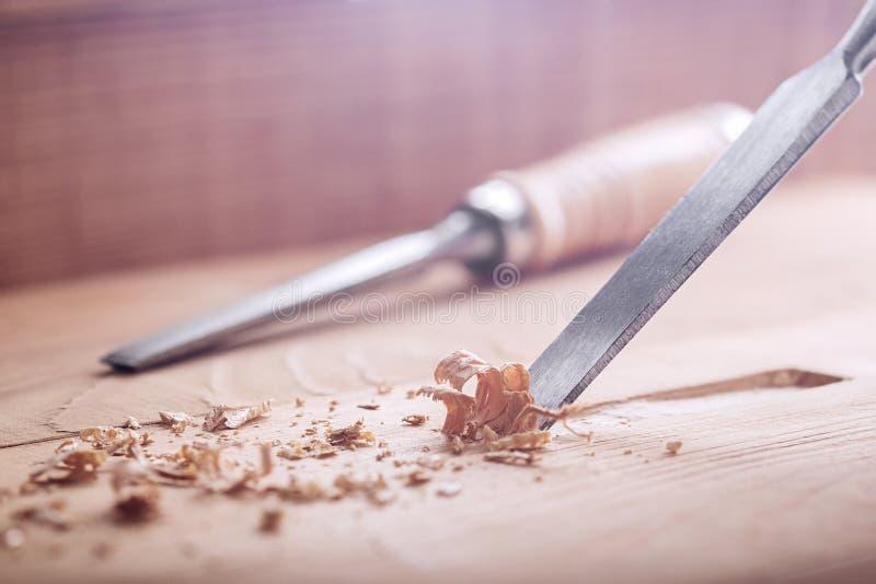 Stechbeitel, der Nut in der alten Kiefernplanke für das Türschloss herausschneidet lizenzfreie stockfotografie