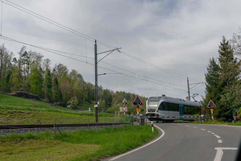 Steckborn TG/Schweiz - 22 April 2019: järnvägkorsning i vårbygd med ett drev som rusar över en gränd två royaltyfri fotografi