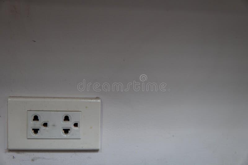 Steckdosen mit der Spinne gewellt auf einer schmutzigen weißen Wand bei einer Ecke des Raumes stockbild