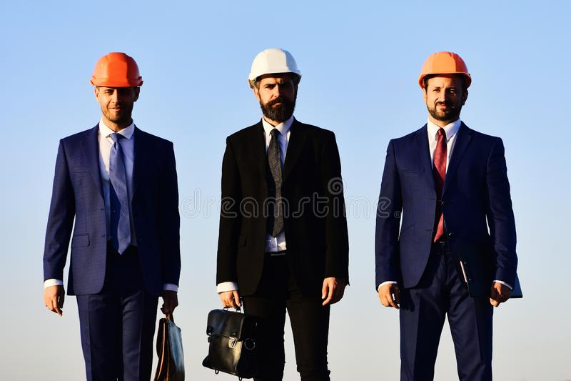 Stedelijk bouw en bedrijfsconcept Arbeiders en ingenieursgreepvergadering stock afbeeldingen