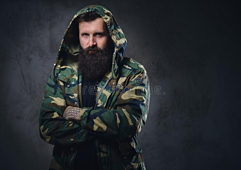 Stedelijk kijk gebaard mannetje met gekruiste wapens gekleed in een camouflagejasje stock foto
