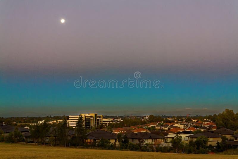 Stedelijk landschap bij blauw uur door volle maan stock fotografie