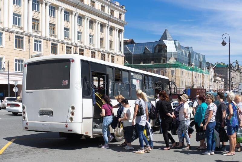 Stedelijk landschap met een witte bus en een rij van passagiers stock afbeeldingen