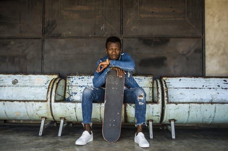 Stedelijk levensstijlportret van jonge knappe en aantrekkelijke zwarte de mensenzitting van afro Amerikaanse skateboarder op stad royalty-vrije stock foto