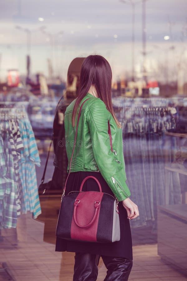 Stedelijk meisje die in winkelvensters kijken stock foto