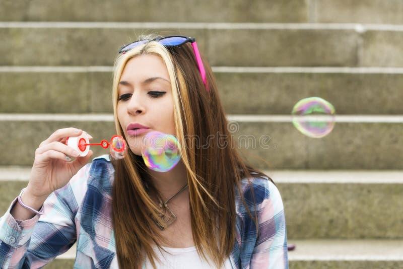 Stedelijk portret van het mooie jonge meisje spelen met bellen stock foto