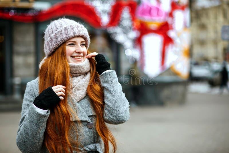 Stedelijk portret van vrolijke gembervrouw met het lange haar warm dragen stock afbeelding