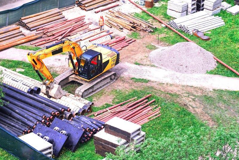 Stedelijk tractormateriaal om te graven De pijpen zijn klaar voor het leggen in de grond Het graafwerktuig is klaar om een geul t stock foto's