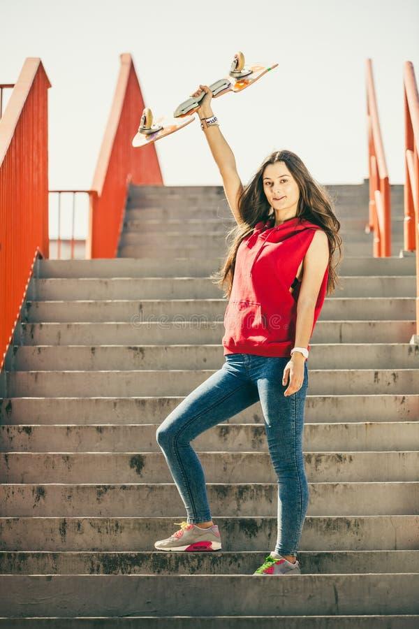 Stedelijk vleetmeisje met skateboard stock foto's