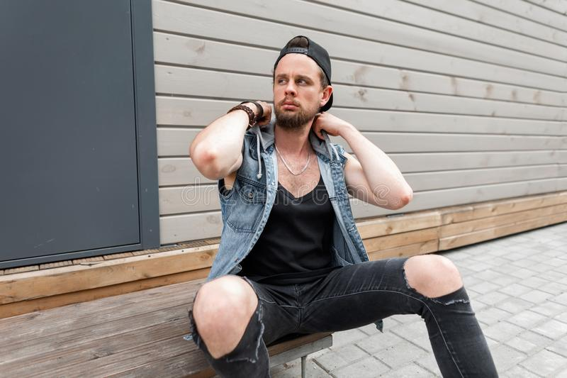 Stedelijke aantrekkelijke jonge mens met een baard in een modieus GLB in een modieus denimvest in een zwarte t-shirtzitting royalty-vrije stock afbeeldingen